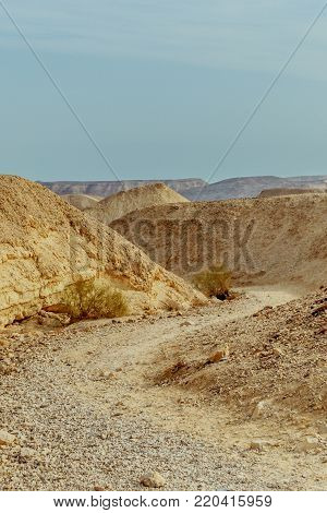 View on dry desert sunny land near dead sea in Israel. Valley of sand, mountains and stones in hot middle east tourism place. Scenic outdoor infinity on wild land. Summer heat and nobody on photo