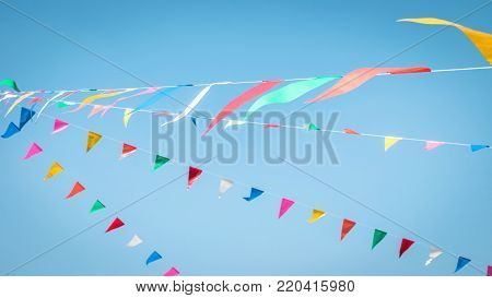 Fair flag blur bunting background hanging on blue sky for fun festa party event, summer holiday farm feast celebration, carnival festival event, park or street design decoration element