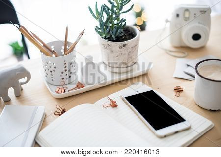Wooden home office desk flat lay with coffe, smartphone and succulents, stylish freelancers workspace, phone screen mock-up