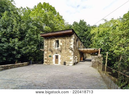 Restored stone building of the Monastery of Caaveiro  dating back to the 10th century and welcoming hermits of the area, in Galicia, Spain. A very green landscape without people