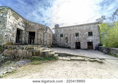 Exterior view of stone buildings of the ancient monastery of Caaveiro dating from the tenth century and which welcomed hermits of the area, in Galicia, Spain. With a mountainous landscape and very green