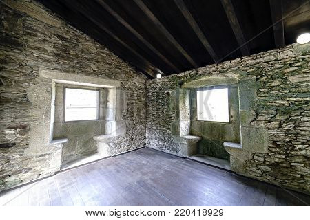 Interior view of the second floor of the bedroom of the hermitage monks of the ancient monastery of Caaveiro dating from the tenth century and which hosted hermits of the area, in Galicia, Spain. Detail of the typical stone seats in the windows