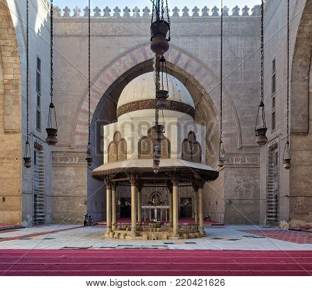 Cairo, Egypt - December 16, 2017: Courtyard of the Mosque of Sultan Hasan with Ablution fountain and huge arch, and few tourists visiting the place at the early morning