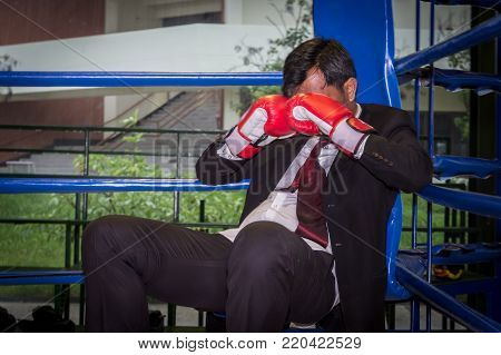 Asian businessman with boxing gloves. Concept of relentless struggle and success