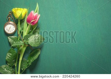 Yellow and pink flowers and a pocket watch - Yellow rose and a pink tulip sprinkled with water and a vintage pocket clock near them on a dark green background.