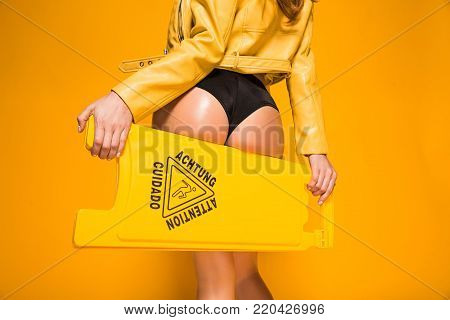 cropped image of sexy woman holding wet floor sign on orange