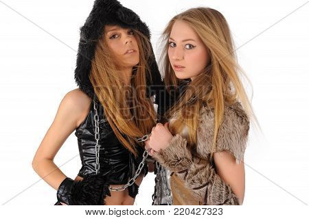 Young beautiful women in cat and barbarian costumes. Isolated over white background