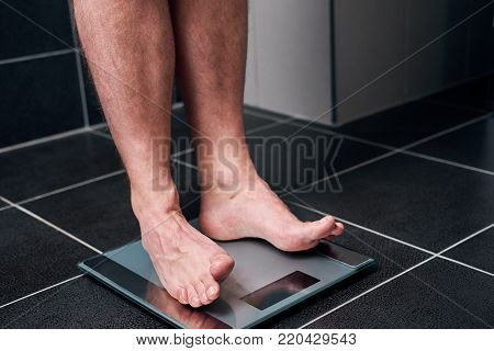 Man On The Scale In The Bathroom.