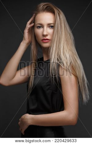 sexy fashion model with long hair, young European attractive, beautiful eyes, perfect skin is posing in studio for glamour vogue test photo shoot showing different poses. Picture taken in the studio on a gray background.
