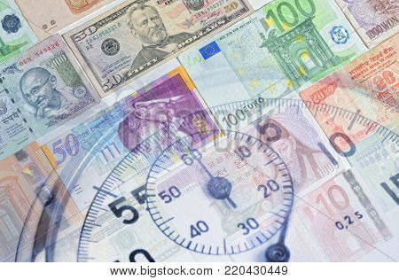 Background of the banknotes of various currencies and analog stopwatch.