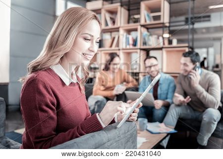 Useful gadget. Joyful occupied smart woman sitting in the room near her friends smiling and using the tablet.