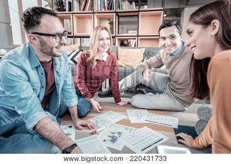Work with team. Pleasant satisfied occupied employees sitting in the office on the floor around documents having discussion and smiling.