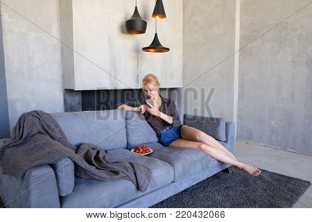Pretty girl rests from bustle of city and sits on Internet with mobile phone, looks ahead and tries ripe red strawberry berries, sits on gray soft sofa in stylish living room with gray walls. Young European-looking woman with blond hair gathered from abov