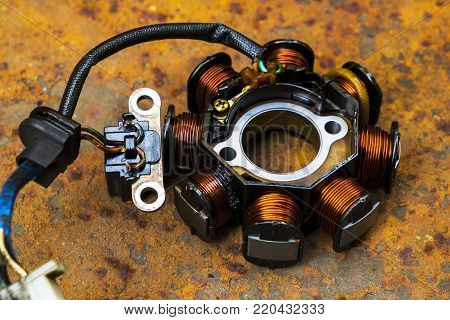Close up of Used Motorcycle Stator on a Rusty Metal Sheet Background.