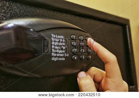 Using forefinger / index finger pushing number button on black safe to unlock safe or set password for safe show concept of safety