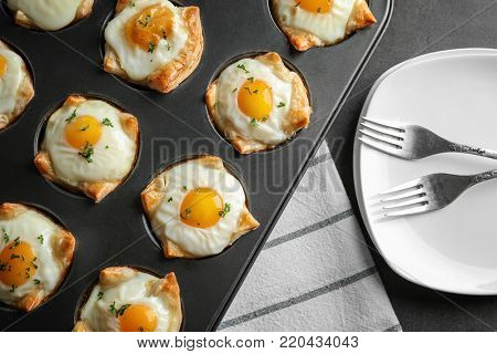 Baking mold with tasty eggs in dough on table