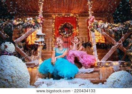 Two pretty little girls dressed in beautiful festive dresses are sitting on the porch of a house decorated for Christmas. Time for miracles. Merry Christmas and Happy New Year.