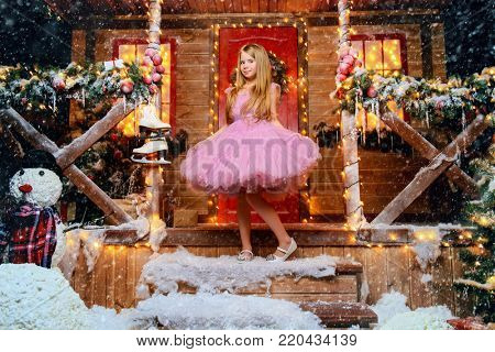 Happy child girl in a beautiful pink dress stands near the house decorated for Christmas. Time for miracles. Merry Christmas and Happy New Year.
