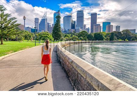 Sydney city girl tourist walking in urban park with skyscrapers skyline in the background. Australia travel vacation in the summer. Australian people lifestyle living.