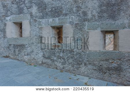 detail of three slits of an old castle /the slits were openings in the wall of fortress to spy on and to use the  weapons against the enemies detail of three slits of an old castle /the slits were openings in the wall of fortress to spy on and to use t