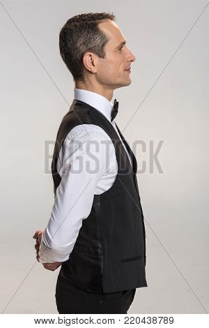 Realize desire. Focused earnest male waiter posing on the grey background and  placing hands behind back while listening