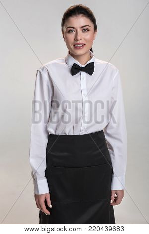 Waitress uniform.  Cheerful charming professional waitress smiling  while looking at the camera and working
