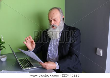 Grandpa working on pension communicates with potential business partners and negotiates bluetooth headset, reads and dictates information from documents, sits in modern office at table with laptop.