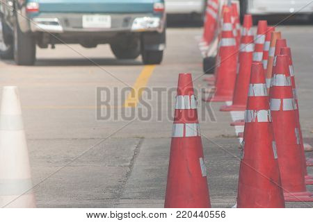 Row of orange traffic cones setting on roadway beside parking lot. (Selective focus)