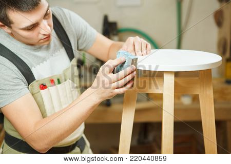Carpenter polish round chair in workshop. Woodworker in apron work with wooden furniture, craftsman at work, professional handyman