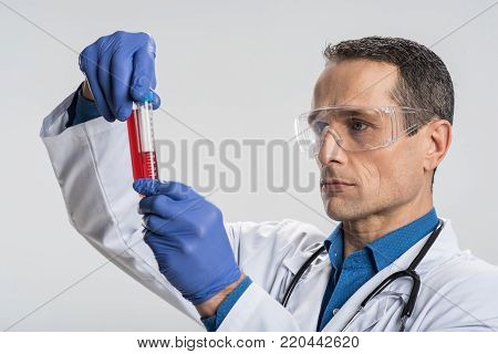 Patients sample. Serious ambitious  male laboritorian wearing  latex gloves while scrutinizing  blood sample and conducting research