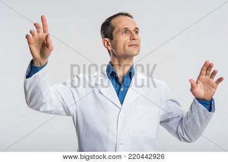 Do it now. Ambitious nice male physician waving  hands  and looking aside while  manipulating