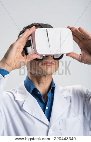 Cutting edge technology.  Focused earnest male doctor using  VR glasses while working and  conducting study