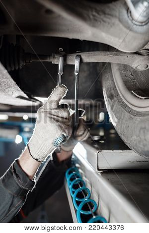 car mechanic examining car suspension of lifted automobile at repair service station.