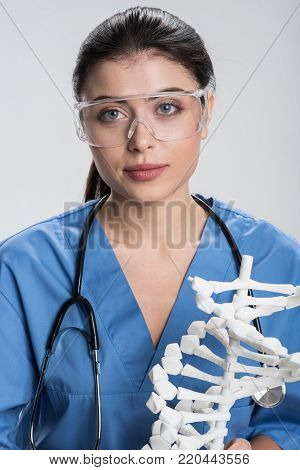 Biological enigma.  Serious beautiful female doctor has stethoscope while wearing safety glasses and looking straight