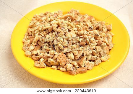 Chopped walnuts and cookie crumbs in a yellow plate on a light coarse tablecloth. Ingredients for baking.