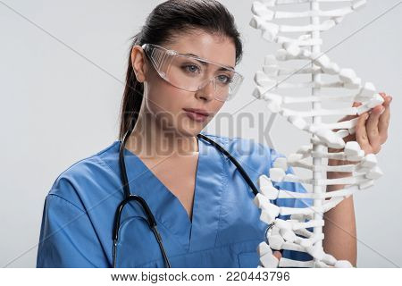 Complex biology. Focused earnest female doctor  caressing DNA model while testing it and looking for solution