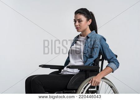 Serious problem. Beautiful nice crippled woman posing on the isolated background while sitting in the wheelchair and thinking