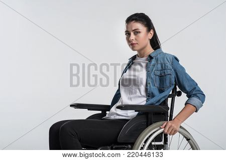 Future ahead. Young budding crippled woman looking at the camera while using wheelchair and waiting