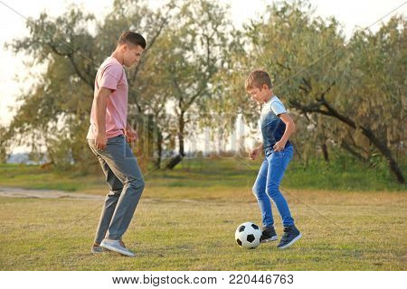 Father and his son playing soccer in countryside