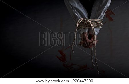 Woman hostage tied of hands with rope sexual robber concept, bandit sexual abuse or female in abandoned house with blood on black background, Copy space the left
