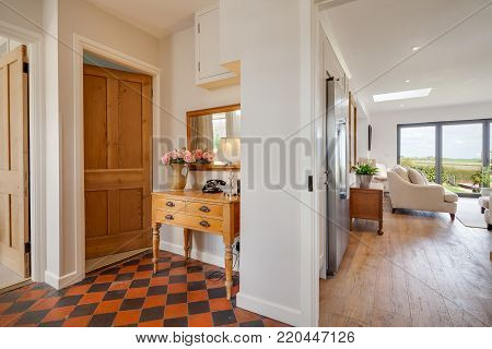 Entrance lobby in private home with traditional tiled floor, table with telephone, vase and lamp opening through to an open plan living area with views beyond through a large window