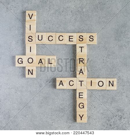 Wooden cubes crossword of Success, Vision, Strategy, Goal, Action on wood background