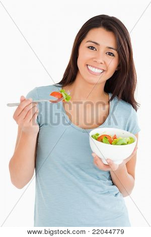 Good looking woman eating a bowl of salad while standing against a white background
