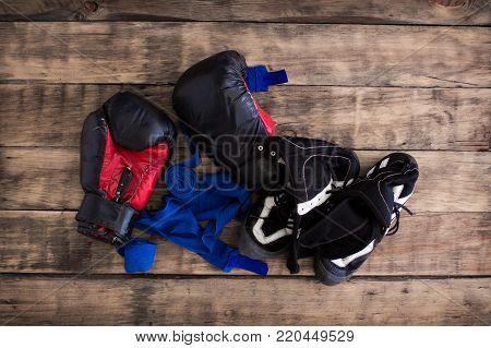 Old Black Boxing Gloves on  Vintage Wooden Grunge Background Copy Space