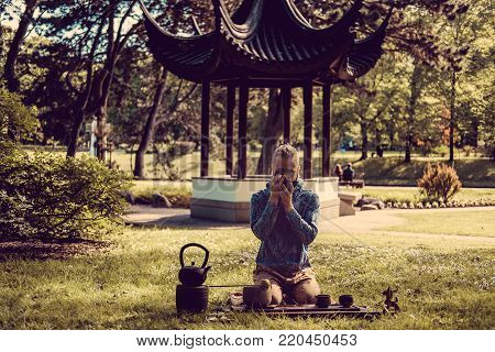 Caucasian man performed chinese tea ritual in summer park with traditional chinese arbour on background.