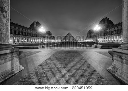 PARIS, FRANCE - DECEMBER 02, 2017: Black and white view of famous Louvre Museum with Louvre Pyramid at evening. Louvre Museum is one of the largest and most visited museums worldwide