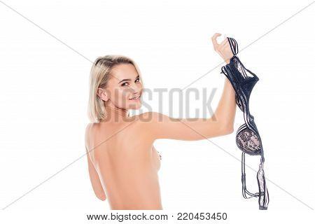 beautiful naked girl taking off black bra, isolated on white