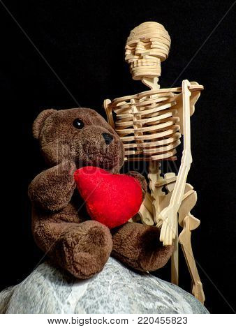 Love can share everyone: Teddy bear shares love with lonely skeleton. Kind beings can share love with everyone.