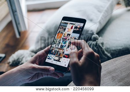 Moscow, RUSSIA - August 20th, 2017: Young woman holding smartphone with search page screen of Instagram application. Instagram is largest and most popular photograph social networking.