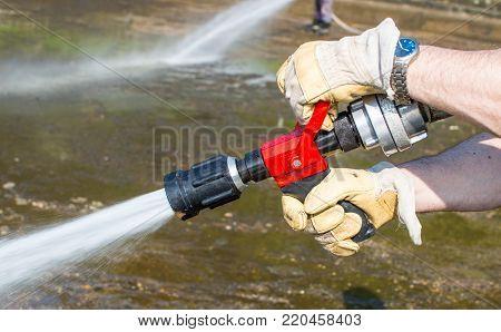 Red fire  hose eliminating mud after flooding. poster